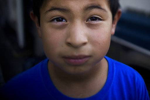 John Ruiz, 9, poses for a photo in front of the RV where he lives with his family on Monday, Oct. 23, 2017, in Mountain View, Calif. His parents and four siblings moved into the camper after they could no longer afford the rent in an apartment. John dreams of his family having a successful life together and maybe ending up in mansion _ a home that might have swimming pool and backyard. Or at least one big enough to have his own room.