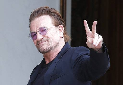 FILE - In this Monday, July 24, 2017 file photo, U2 singer Bono makes a peace sign as he arrives for a meeting at the Elysee Palace, in Paris, France. Leaked papers revealing investments in tax havens by the world's wealthy suggest U2 frontman Bono used a company based in low-tax Malta to buy part of a shopping mall in Lithuania, it was announced on Monday Nov. 6.