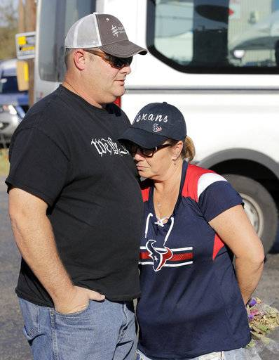 Rebecca Thompson, right, places her head on her husband Jim's chest while visiting a makeshift memorial near the First Baptist Church, Monday, Nov. 6, 2017, in Sutherland Springs, Texas, where a mass shooting occurred Sunday. Texas officials confirmed Devin Patrick Kelley as the shooter who killed at least 26 people and wounded about 20 others at the church.