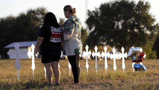 Laura Torres, right, and Sonia Yanez visit a line of crosses before a vigil for the victims of Sunday's First Baptist Church shooting, Monday, Nov. 6, 2017, in Sutherland Springs, Texas. A man opened fire inside the church in the small South Texas community on Sunday, killing more than 20 and wounding many.