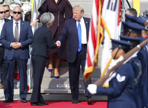 U.S. President Donald Trump, center, is welcomed by South Korean Foreign Minister Kang Kyung-wha upon arrival at Osan Air Base in Pyeongtaek, South Korea, Tuesday, Nov. 7, 2017. Trump arrived here on the second leg of his five-nation Asian tour and will hold a summit with South Korean President Moon Jae-in.