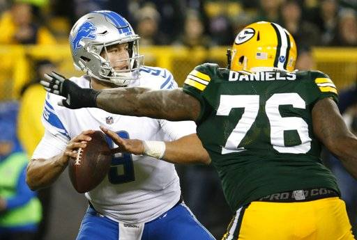 Detroit Lions' Matthew Stafford drops back with Green Bay Packers' Mike Daniels rushing during the first half of an NFL football game Monday, Nov. 6, 2017, in Green Bay, Wis.