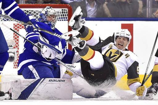 Vegas Golden Knights left wing David Perron (57) falls over Toronto Maple Leafs goalie Frederik Andersen (31) during the second period of an NHL hockey game, Monday, Nov. 6, 2017, in Toronto. (Frank Gunn/The Canadian Press via AP)