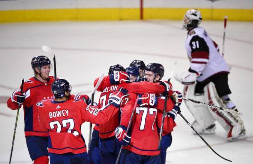 Washington Capitals defenseman John Carlson (74), T.J. Oshie (77), Madison Bowey (22), and others celebrate after Carlson's game winning goal in overtime of an NHL hockey game as Arizona Coyotes goalie Scott Wedgewood (31) skates by at top, Monday, Nov. 6, 2017, in Washington. The Capitals won 3-2 in overtime.