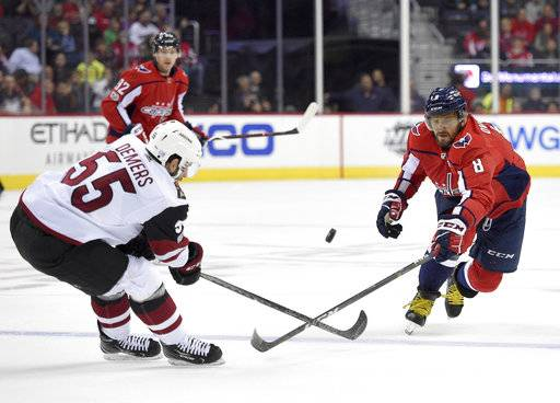 Washington Capitals left wing Alex Ovechkin (8), of Russia, battles for the puck against Arizona Coyotes defenseman Jason Demers (55) during the first period of an NHL hockey game, Monday, Nov. 6, 2017, in Washington.