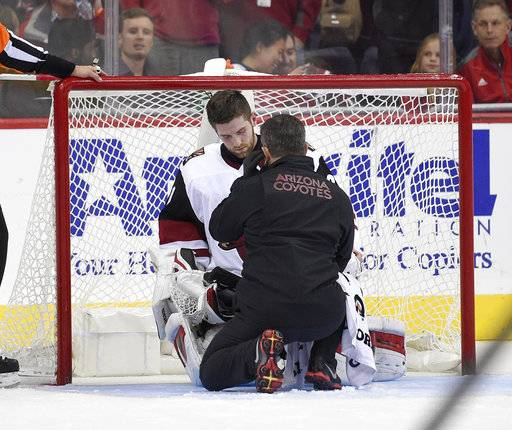 Arizona Coyotes goalie Scott Wedgewood, back, is tended to during the second period of an NHL hockey game against the Washington Capitals, Monday, Nov. 6, 2017, in Washington. Wedgewood stayed in the game.
