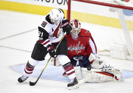Washington Capitals goalie Braden Holtby, right, stops the puck against Arizona Coyotes center Derek Stepan (21) during the third period of an NHL hockey game, Monday, Nov. 6, 2017, in Washington. The Capitals won 3-2 in overtime.