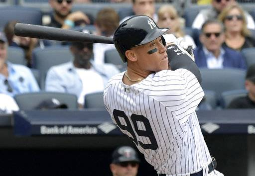 FILE - In this Wednesday, Sept. 20, 2017 file photo, New York Yankees' Aaron Judge follows through on a two-run home run during the third inning of a baseball game against the Minnesota Twins at Yankee Stadium in New York. Yankees slugger Aaron Judge is a finalist for AL MVP and Rookie of the Year, giving him a chance to become just the third player to win the awards in the same year. The Baseball Writers' Association of America revealed the finalists for its major awards on Monday night, Nov. 6, 2017.