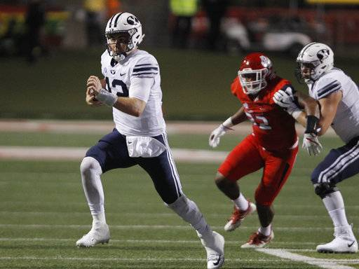 BYU's quaterback Tanner Mangum tries to outrun a Fresno State defender during the first half of an NCAA college football game in Fresno, Calif., Saturday, Nov. 4, 2017.