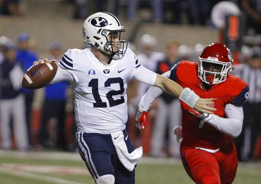 BYU's Tanner Mangum tries to complete a pass as Fresno State's Jeffrey Allison chases during the first half of an NCAA college football game in Fresno, Calif., Saturday, Nov. 4, 2017.