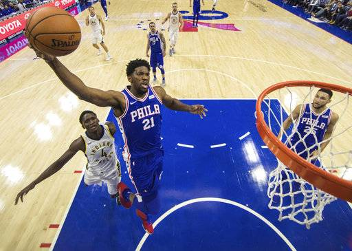 Philadelphia 76ers' Joel Embiid goes up for a shot with Indiana Pacers' Victor Oladipo, left, trailing during the first half of an NBA basketball game, Friday, Nov. 3, 2017, in Philadelphia. The 76ers won 121-110.