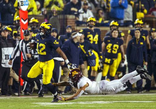 Michigan running back Chris Evans (12) rushes, avoiding a tackle from Minnesota defensive back Jacob Huff (2), in the second quarter of an NCAA college football game in Ann Arbor, Mich., Saturday, Nov. 4, 2017.