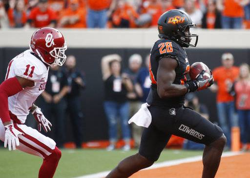 Oklahoma State wide receiver James Washington (28) runs into the end zone with a touchdown in front of Oklahoma cornerback Parnell Motley (11) in the first half of an NCAA college football game in Stillwater, Okla., Saturday, Nov. 4, 2017.