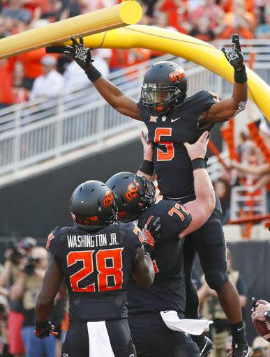 Oklahoma State running back Justice Hill (5) celebrates his touchdown with teammates Johnny Wilson (72) and James Washington (28) in the first half of an NCAA college football game against Oklahoma in Stillwater, Okla., Saturday, Nov. 4, 2017.