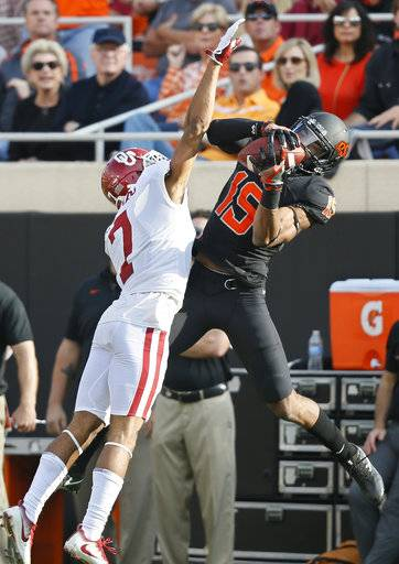 Oklahoma State wide receiver Chris Lacy (15) catches a pass in front of Oklahoma cornerback Jordan Thomas (7) in the first half of an NCAA college football game in Stillwater, Okla., Saturday, Nov. 4, 2017.