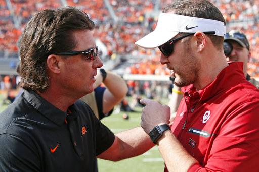 Oklahoma State head coach Mike Gundy, left, talks with Oklahoma head coach Lincoln Riley, right, before their NCAA college football game in Stillwater, Okla., Saturday, Nov. 4, 2017.