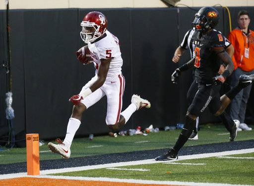 Oklahoma wide receiver Marquise Brown (5)t scores in front of Oklahoma State cornerback Rodarius Williams (8) in the second half of an NCAA college football game in Stillwater, Okla., Saturday, Nov. 4, 2017. Oklahoma won 62-52.