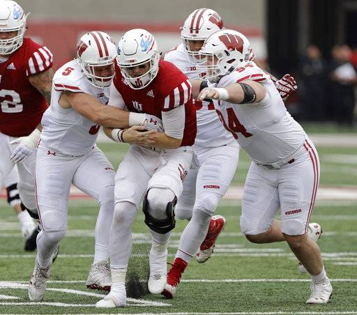 Indiana quarterback Richard Lagow (21) is tackled by Wisconsin's Garret Dooley (5) and Conor Sheehy (94) during the second half of an NCAA college football game, Nov. 4, 2017, in Bloomington, Ind. Wisconsin won 45-17.