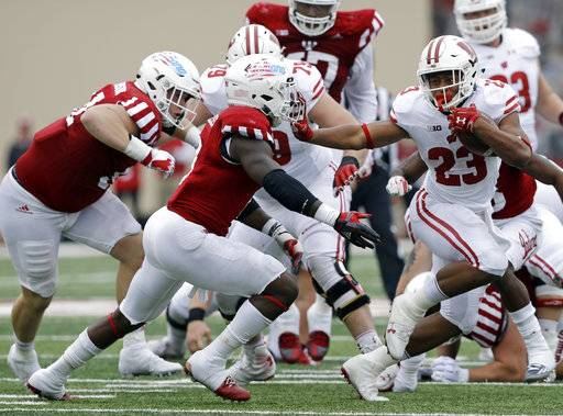 Wisconsin running back Jonathan Taylor (23) runs past Indiana's Tegray Scales (8) for a 32-yard touchdown run during the second half of an NCAA college football game, Nov. 4, 2017, in Bloomington, Ind. Wisconsin won 45-17.