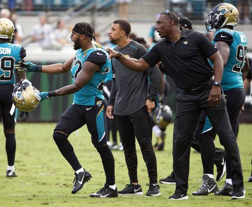 Jacksonville Jaguars cornerback Aaron Colvin is held back as he shouts at Cincinnati Bengals players during an altercation in the first half of an NFL football game, Sunday, Nov. 5, 2017, in Jacksonville, Fla.