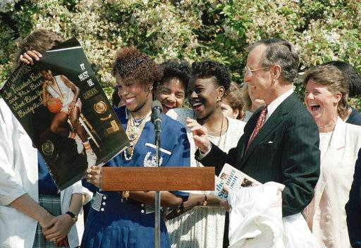 FILE - In this April 20, 1989, file photo, Bridgette Gordon, left, a member of the University of Tennessee's national championship women's basketball team, presents President Bush with an autographed photo of herself during a White House Rose Garden reception for the team. Looking on are teammates Tonya Edwards, left center, and Melissa McCray. Bridgette Gordon starred on two of Tennessee's national championship teams and reached the Final Four each of her four seasons with the Lady Volunteers. Now the U.S. Olympic gold medalist is back at her alma mater as an assistant coach trying to help Tennessee regain the prominence it enjoyed during her own playing career.