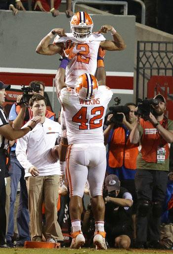 Clemson's Christian Wilkins (42) lifts quarterback Kelly Bryant (2) following Bryant's touchdown against North Carolina State during the second half of an NCAA college football game in Raleigh, N.C., Saturday, Nov. 4, 2017. Clemson won 38-31.
