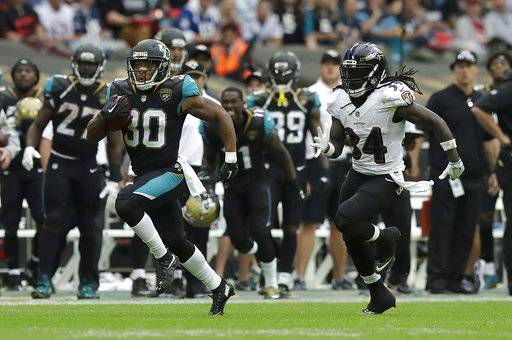 FILE - In this Sept. 24, 2017, file photo, Jacksonville Jaguars' Corey Grant, left, runs past Baltimore Ravens' Alex Collins (34) during the second half of an NFL football game at Wembley Stadium in London. With the NFL at the halfway point, plenty of teams have dipped into the playbooks for something special. Jaguars running back Corey Grant took a direct snap 58 yards on a fake punt in a big win over Baltimore in London.