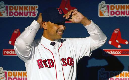 Alex Cora adjusts his baseball cap as he is introduced as the Boston Red Sox baseball teams new manager during a news conference in Boston, Monday, Nov. 6, 2017.