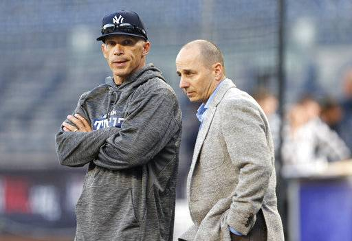"FILE - In this Oct. 3, 2017, file photo, New York Yankees manager Joe Girardi, left, and general manager Joe Girardi chat on the field before the team's American League wild-card playoff baseball game against the Minnesota Twins, in New York. Cashman was concerned with Girardi's ""connectivity and communication level� with players in deciding to replace him as New York's manager. Cashman decided it was time for a ""new voice� and a ""fresh voice� in the job and said there may be a ""shelf life� to a manager's tenure with a team."