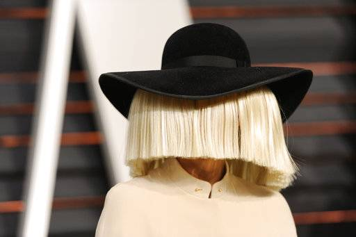 FILE - In this Feb. 22, 2015, file photo, Sia arrives at the 2015 Vanity Fair Oscar Party in Beverly Hills, Calif. Sia tweeted a nude photo of herself on Nov. 6, 2017, after learning that someone was trying to sell nude paparazzi photos of her. (Photo by Evan Agostini/Invision/AP, File)