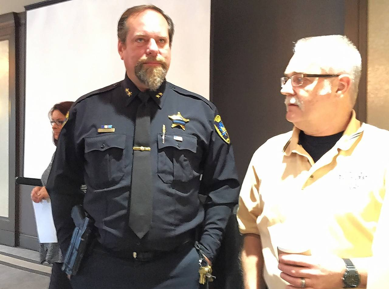 Carol Stream Deputy Police Chief John Jungers, left, confers with colleagues at a AAA conference Tuesday about repercussions if Illinois lawmakers legalize recreational marijuana.