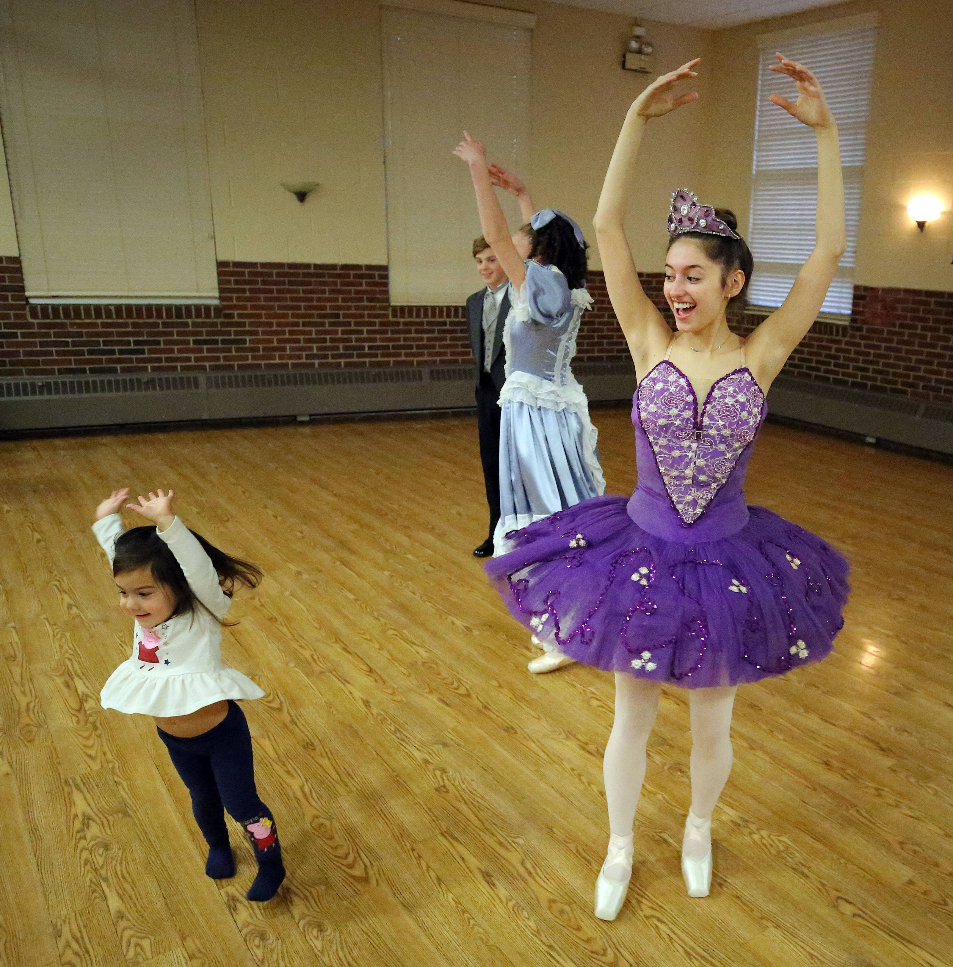 "Two-year-old Anne Sabbin of Libertyville dances with 16-year-old Katie Waldvogel of Green Oaks, who is the Sugar Plum Fairy, as Cook Park Library and Dance Center North teamed up for ""The Nutcracker"" story time at the Civic Center in Libertyville Tuesday."
