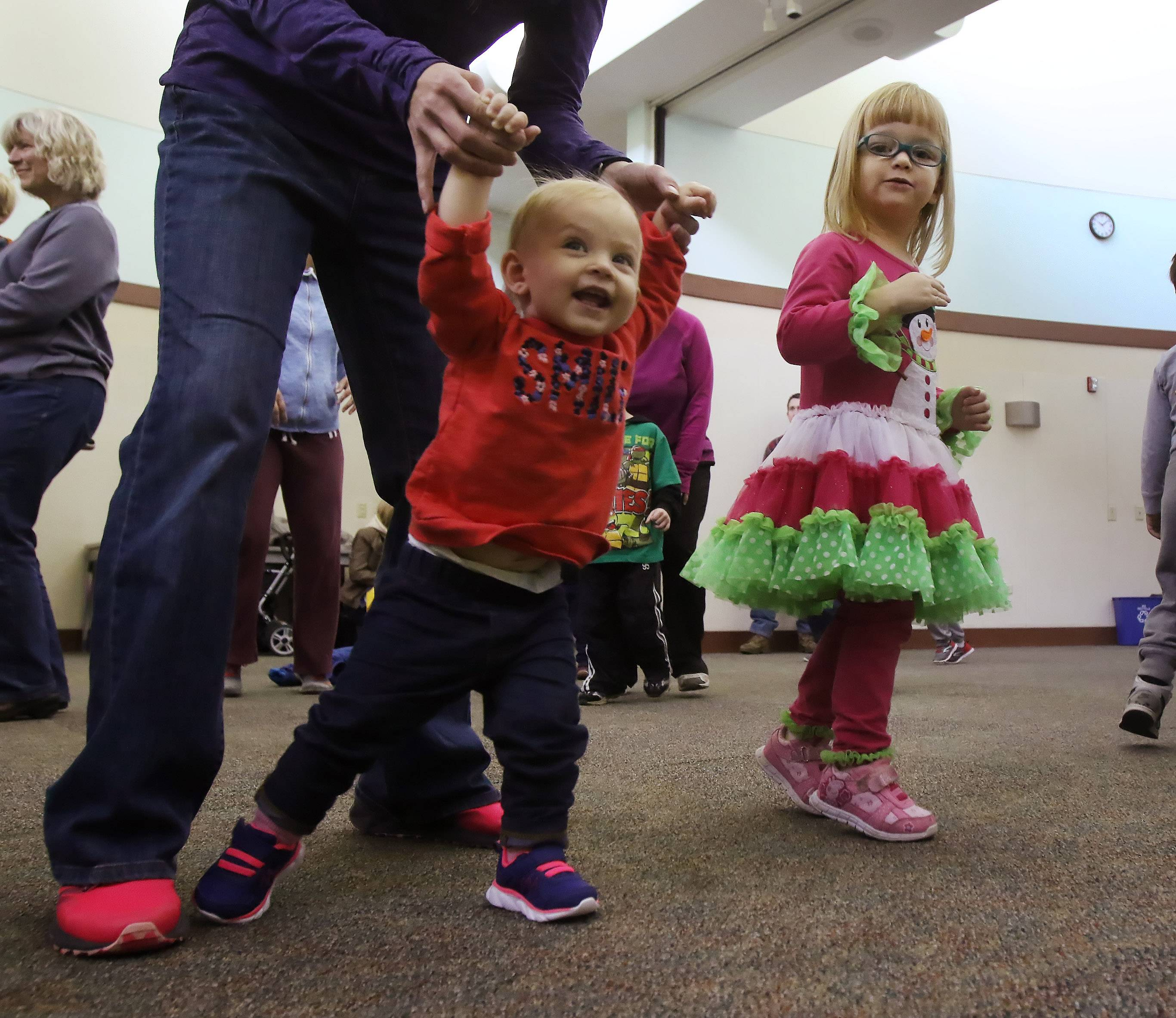 Layla Lock of Gurnee dances with her mother, Crystal, as Emma Teal, 3, of Lindenhurst watches Tuesday during the Family Dance Party at Lake Villa District Library. About 60 children, parents and caregivers danced and played instruments during the musical program.