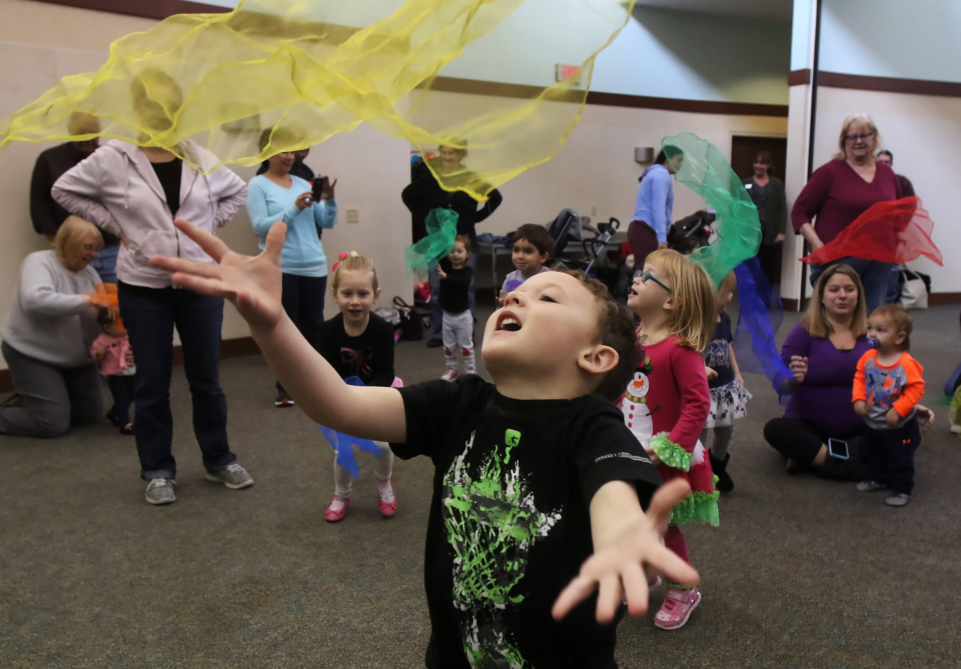 L.J. Haley, 5, throws up a scarf with other children Tuesday during the Family Dance Party at Lake Villa District Library. About 60 children, parents and caregivers danced and played instruments during the musical program.