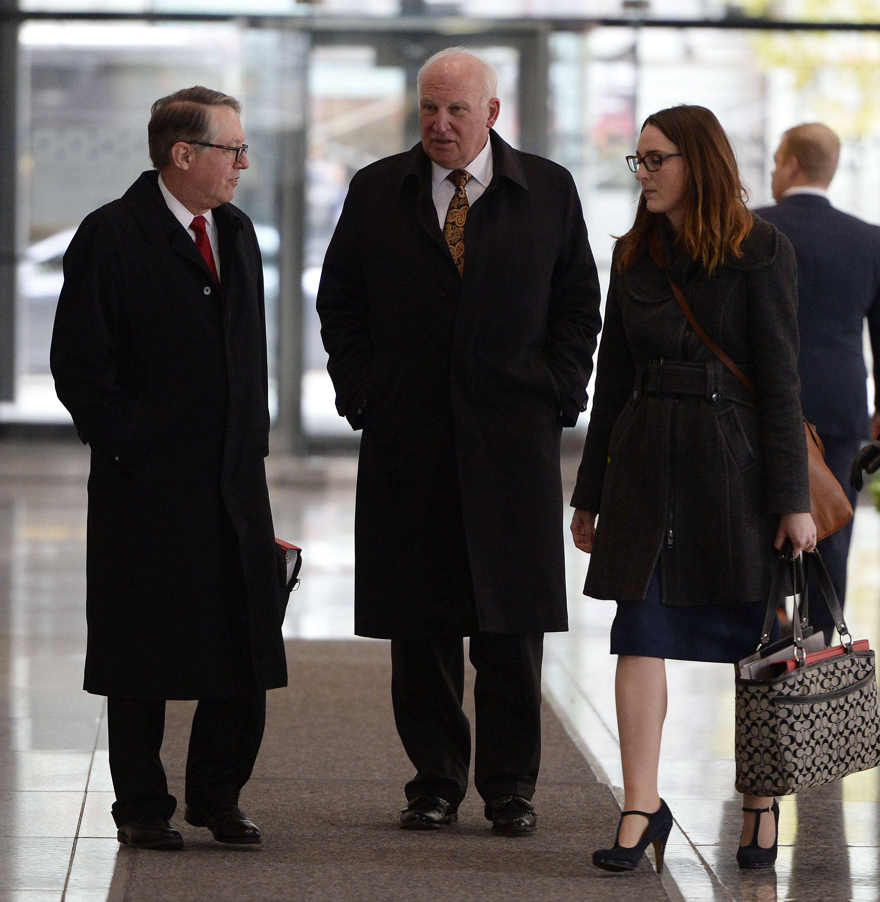 "Former College of DuPage President Robert Breuder, center, said Tuesday was the first time he's been in a federal courthouse and he found it somewhat ""shocking"" to hear his name mentioned aloud."