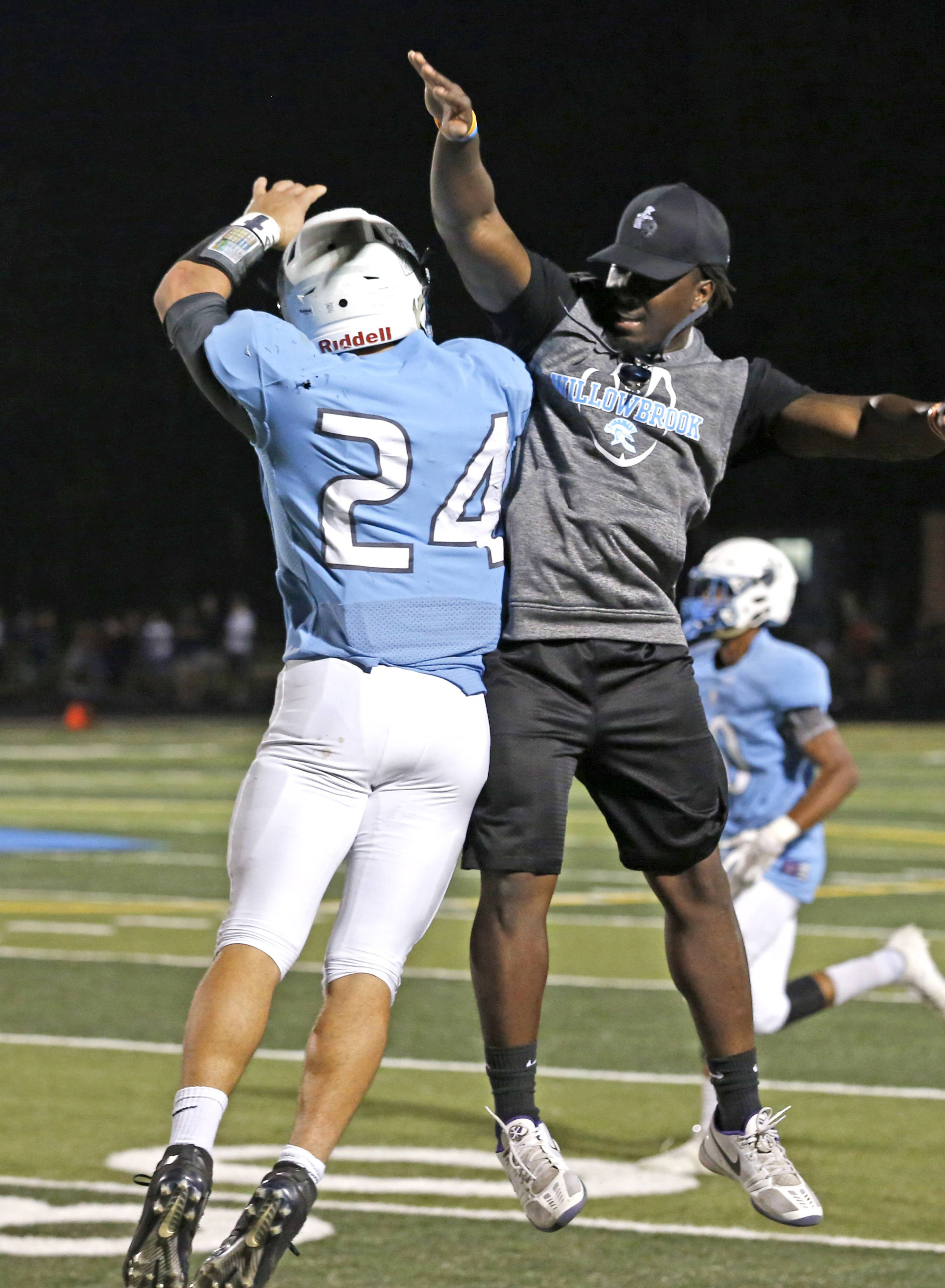 Willowbrook High School's Jack Jessen (24) celebrates his first half touchdown with coach Khyree Copeland, right, against Addison Trail, September 15, 2017, in Villa Park.