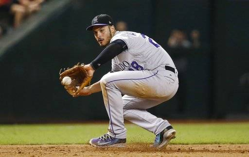 FILE - In this Tuesday, Sept. 12, 2017 file photo, Colorado Rockies' Nolan Arenado gets his glove on a grounder hit by Arizona Diamondbacks' Chris Iannetta before throwing to first base for the out during the eighth inning of a baseball game in Phoenix. Rockies third baseman Nolan Arenado has won his fifth consecutive Gold Glove Award, while Twins center fielder Byron Buxton headlines a group of six first-time winners. (AP Photo/Ross D. Franklin, File)