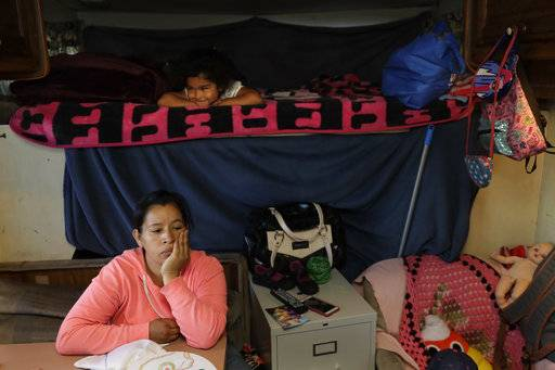In this photo taken Oct. 5, 2017, Delmi Ruiz, bottom, sits inside and RV where here family lives and sleeps under her daughter Delmi, 4, top, in Mountain View, Calif. The Ruiz Hernandez family was left homeless after the landlord in the apartment they rented hiked their rent beyond what they could afford. The booming economy along the West Coast has led to an historic shortage of affordable housing and has upended the stereotypical view of people out on the streets.