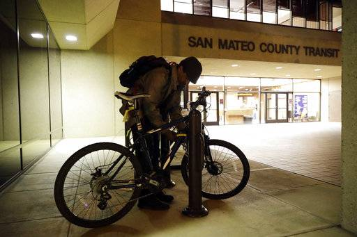 In this photo taken Oct. 25, 2017, Albert Brown III, who works as a security officer, locks his bike in front of his workplace in San Carlos, Calif. Brown recently signed a lease for half of a $3,400 two-bedroom unit in Half Moon Bay, about 13 miles from his job. He can barely afford the rent on his $16-an-hour salary, even with overtime, but the car that doubled as his home needed a pricey repair and he found a landlord willing to overlook his lousy credit.