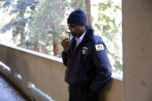 In this photo taken Oct. 26, 2017, Albert Brown III, who works as a security officer, talks to a friend after the end of his shift in San Carlos, Calif. Brown recently signed a lease for half of a $3,400 two-bedroom unit in Half Moon Bay, about 13 miles from his job. He can barely afford the rent on his $16-an-hour salary, even with overtime, but the car that doubled as his home needed a pricey repair and he found a landlord willing to overlook his lousy credit.