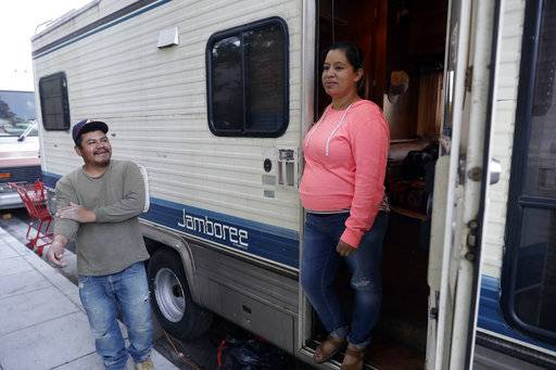 Delmi Ruiz, right, and her husband Benito Hernandez chat outside their RV where their family lives and sleeps on Thursday, Oct. 5, 2017, in Mountain View, Calif. The Ruiz Hernandez was family was left homeless after the landlord in the apartment they rented hiked their rent beyond what they could afford. A homeless crisis of unprecedented proportions is rocking the West Coast, and its victims are being left behind by the very things that mark the region's success: soaring housing costs, rock-bottom vacancy rates and a roaring economy that waits for no one.