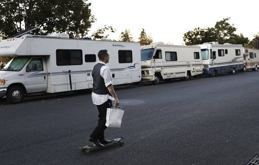 In this photo taken Oct. 5, 2017, a man skates past a row of RVs where people live and sleep in the heart of silicon valley in Mountain View, Calif. Apartments across the street start at over $3,000 a month. The booming economy along the West Coast has led to an historic shortage of affordable housing and has upended the stereotypical view of people out on the streets. Reporting by The Associated Press finds that many of them are employed, working as retail clerks, plumbers, janitors _ even teachers. They go to work, sleep where they can and buy gym memberships for a place to shower.