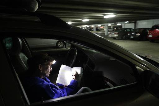 Ellen Tara James-Penney, a lecturer at San Jose State University, prepares her lesson plan inside the station wagon where she sleeps on Tuesday, Oct. 10, 2017, in San Jose, Calif. The booming economy along the West Coast has led to an historic shortage of affordable housing and has upended the stereotypical view of people out on the streets. Reporting by The Associated Press finds that many of them are employed, working as retail clerks, plumbers, janitors _ even teachers. They go to work, sleep where they can and buy gym memberships for a place to shower.