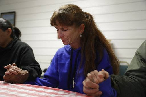 Ellen Tara James-Penney, a lecturer at San Jose State University, prays before receiving a meal at Grace Baptist Church on Tuesday, Oct. 10, 2017, in San Jose, Calif. The booming economy along the West Coast has led to an historic shortage of affordable housing and has upended the stereotypical view of people out on the streets. Reporting by The Associated Press finds that many of them are employed, working as retail clerks, plumbers, janitors _ even teachers. They go to work, sleep where they can and buy gym memberships for a place to shower.