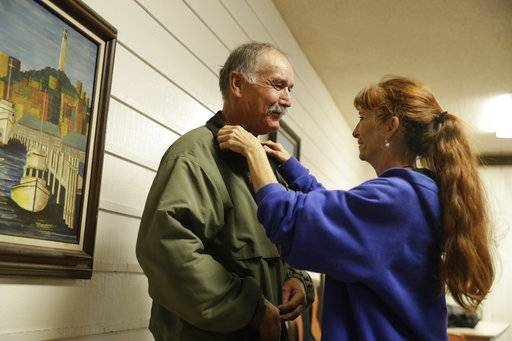 Ellen Tara James-Penney , a lecturer at San Jose State University, right, fixes the collar on her husband Jim's jacket at Grace Baptist Church on Tuesday, Oct. 10, 2017, in San Jose, Calif. The booming economy along the West Coast has led to an historic shortage of affordable housing and has upended the stereotypical view of people out on the streets. Reporting by The Associated Press finds that many of them are employed, working as retail clerks, plumbers, janitors _ even teachers. They go to work, sleep where they can and buy gym memberships for a place to shower.