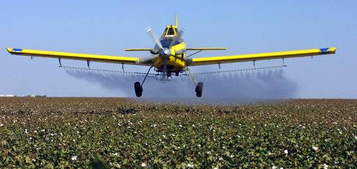 FILE - In this Sept. 25, 2001 file photo, a crop dusting plane from Blair Air Service dusts cotton crops in Lemoore, Calif. California regulators have announced a new rule that bans farmers from using certain pesticides near schools and day care centers. The state's Department of Pesticide Regulation announced the new rule Tuesday, Nov. 7, 2017. The department says the new regulation is among the strictest pesticide in the U.S. (AP Photo/Gary Kazanjian, File)