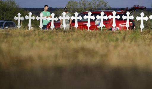 Kevin Blomstrum, left, and Kyle Dahlberg visit a makeshift memorial for victims near the scene of a shooting at the First Baptist Church of Sutherland Springs, Tuesday, Nov. 7, 2017, in Sutherland Springs, Texas. A man opened fire inside the church in the small South Texas community on Sunday, killing more than two dozen and injuring others.