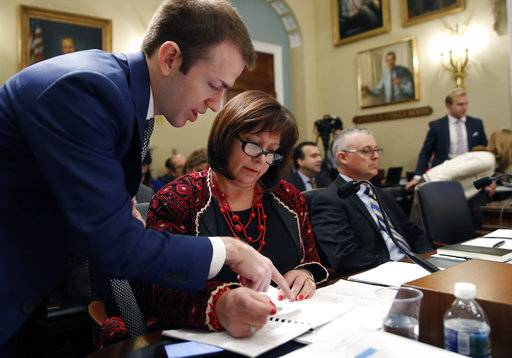 An aide, left, assists Natalie Jaresko, executive director, and Noel Zamot, revitalization coordinator, both of the financial oversight and management board for Puerto Rico, before the start of a House Committee on Natural Resources hearing to examine challenges in Puerto Rico's recovery and the role of the financial oversight and management board, on Capitol Hill, Tuesday, Nov. 7, 2017 in Washington.