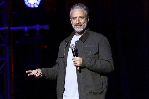 FILE - In this Nov. 10, 2015, file photo, comedian Jon Stewart performs at the 9th Annual Stand Up For Heroes event, in New York.  Stewart, John Oliver, Trevor Noah, Conan O'Brien and Red Hot Chili Peppers will perform at the annual fundraiser for the Bob Woodruff Foundation on Tuesday, Nov. 7, 2017. (Photo by Greg Allen/Invision/AP, File)