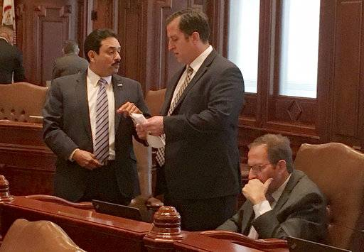 Democratic Senators Tony Munoz D-Chicago, left, and Michael Hastings D-Tinley Park, speak on the floor of the Illinois Senate as Sen. Ira Silverstien, D-Chicago, sits nearby Tuesday Nov. 7, 2017, in Springfield, Ill. The Senate voted to expand power of the newly appointed inspector general to allow her to investigate existing complaints, including one filed last November by legislative activist Denise Rotheimer against Silverstein. (AP Photo by John O'Connor)